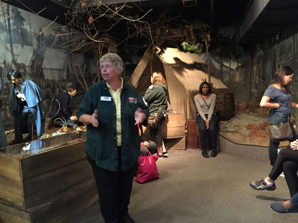 Tour guide Betsy Estilon describes life-- and death-- in camp, while class members peruse the exhibits. The tent in the background belonged to a Civil-War doctor and is one of the Museum's most important possessions.